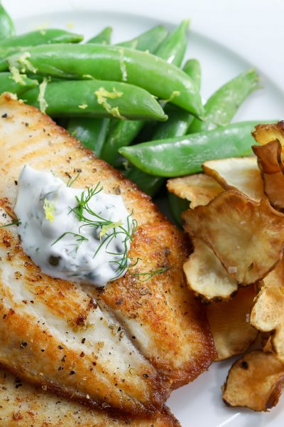 Pan roasted tilapia topped with caper dill sauces served with sunchoke chips
